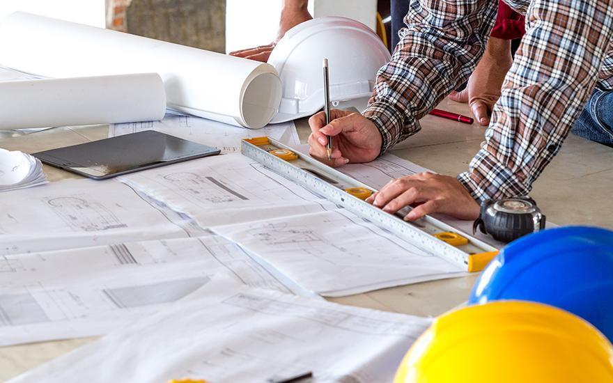 Pracownik budowlany notujący nakartce papieru